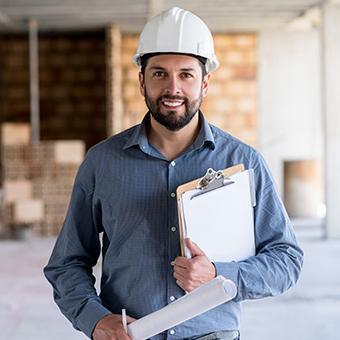 Ein Architekt mit Bauzeichnungen und Helm in einem Neubaukomplex